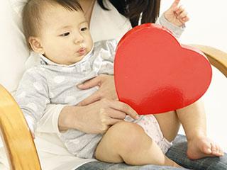 赤ちゃんを膝に座わらせる母親