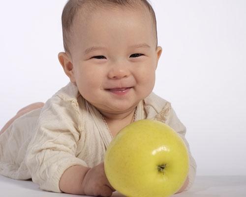 りんごを掴もうとする笑顔の赤ちゃん