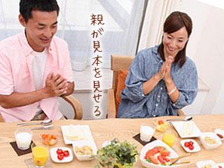 両手を合わせて食事の挨拶をする親