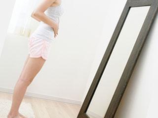 姿見に自分の体を映す女性