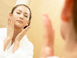 顔に化粧水を両手でつける女性