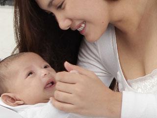 傍の赤ちゃんの手を握る母親