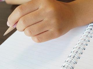 ノートに鉛筆で書き込む子供の手