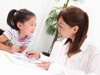 机の上の資料を見ながら子供に説明する母親