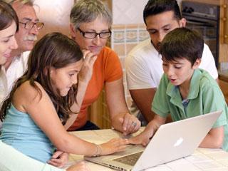 ノートパソコンを子供と家族が囲む