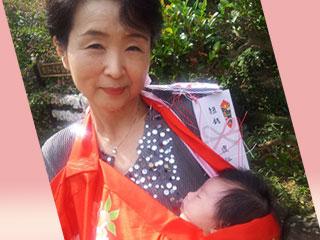 赤ちゃんを抱いてお宮参りする姑
