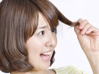 髪の毛を摘んで驚く女性