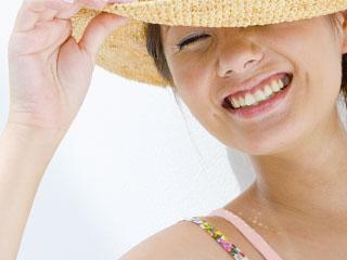 帽子で陽射しをさえぎる女性