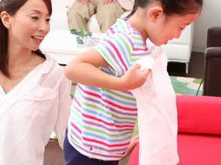 着替えを準備する子供を見守る母親