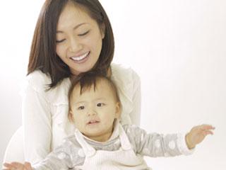 赤ちゃんを抱いて笑顔の母親
