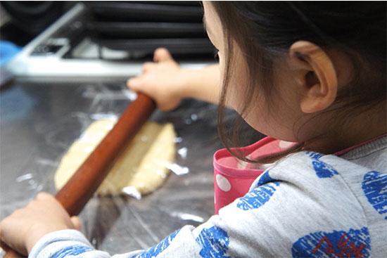 クッキーの生地を伸ばす子供
