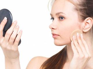手鏡を見ながら化粧崩れを直す女性