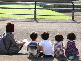 戸外で引率する大人と並んで座る子供達