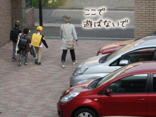 集合住宅の駐車場を子供と母親が歩いていく