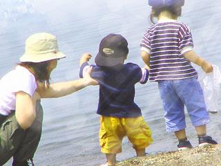 外で遊ぶ子供と世話する母親