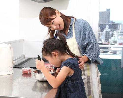 台所で料理を作る子供と見守る母