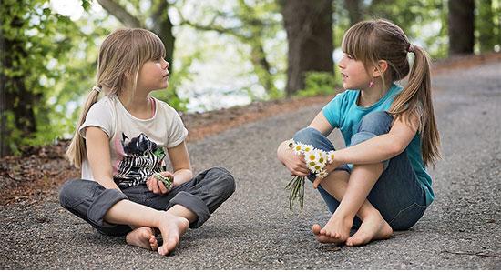 摘んだ花を手に座る女子