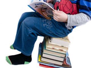 積み重ねた本に腰掛けて読書する少年