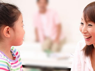 子供と笑顔で話す母親