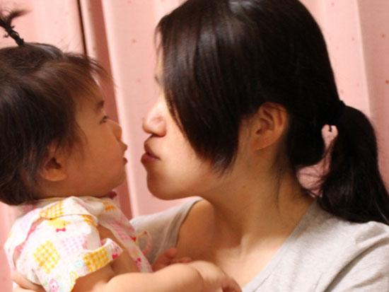 抱き上げた幼児の顔に顔を近づける母親