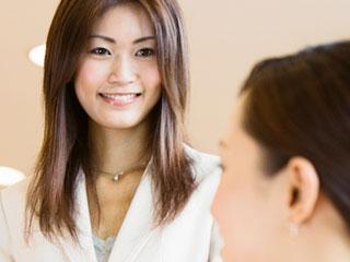 職場で同僚と話す女性