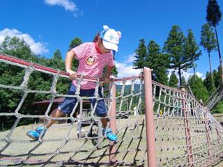 アスレチック運動場で縄梯子で遊ぶ子供