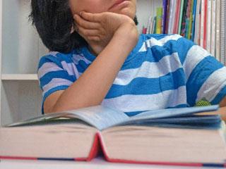 開いた本を前に考える少年