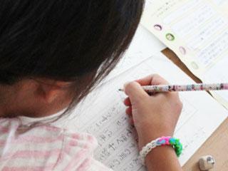 原稿用紙に書く少女