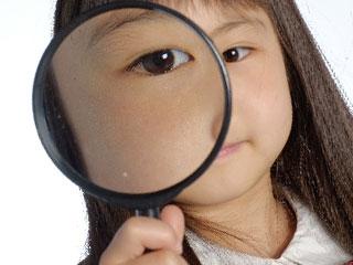 虫眼鏡を覗き込む少女