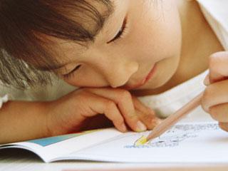 ノートに顔を近づけている子供