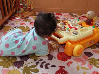 柵の内側で遊ぶ赤ちゃん
