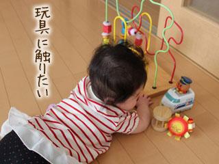 ずりばいの姿勢で玩具に触る赤ちゃん