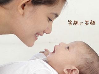 赤ちゃんの笑顔に笑いかける母親