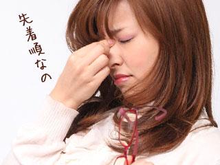 目頭を押さえて疲れた表情の女性