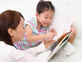 娘に絵本を見せる母親