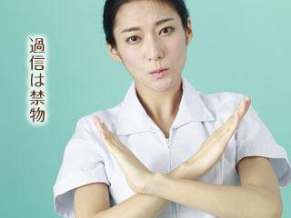 手で×印を出す看護師