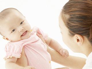 赤ちゃんを抱きかかえて話しかけるママ