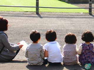 公園で子供が並んで座っている
