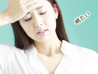 額を押さえながら目を閉じる女性