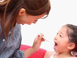 子供の口に体温計を入れる母親