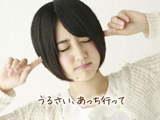 耳を指で塞いで目を閉じる女性