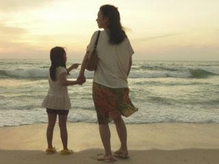 母親と子供が海を前にして手を繋ぐ
