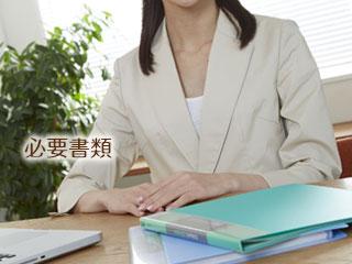 書類フォルダを机に積み重ねてみる女性