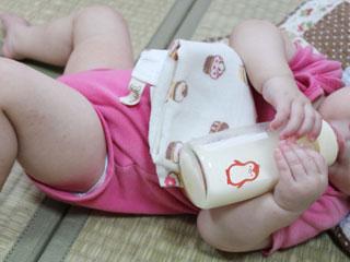 寝そべりながら哺乳瓶からミルクを飲む赤ちゃん