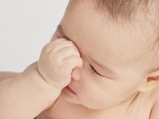 顔に手をやってむずかる赤ちゃん