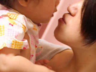 赤ちゃんを抱き上げる母