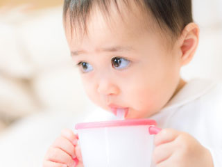 ストローマグで飲む赤ちゃん