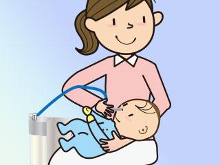 鼻水吸引器を使う母親