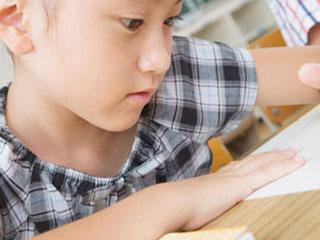 机の上プリントを見る小学生