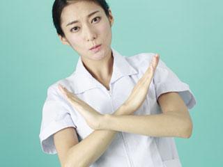腕で×印をする看護師
